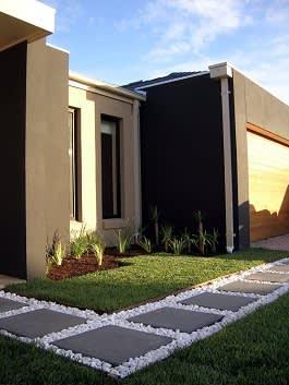 בית מודרני עם שביל אבן בזלת מעובדת על חלוקי נחל בצבע לבן