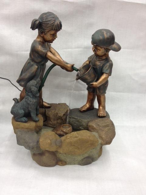 מזרקה ילד וילדה עם צינור מים