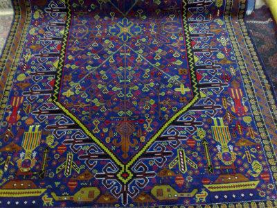 בלוג' גדול עם מוטיבים מלחמתים- שטיח זה למכירה