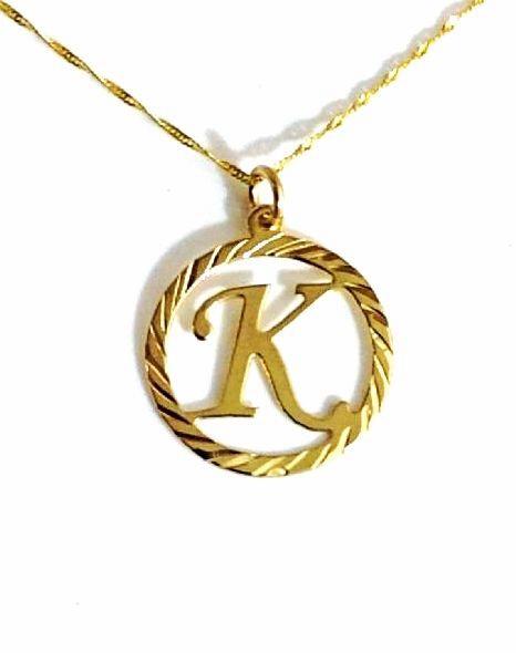 שרשרת זהב עם אות אחת גדולה באנגלית בתוך עיגול ממולא בחריטות יהלום בצורת ספירלה