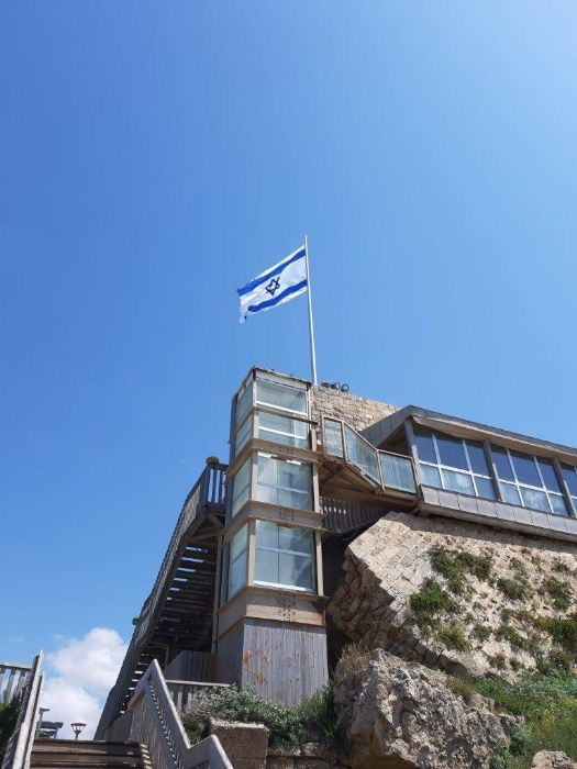 10 meter high conical aluminum flagpole installation on roof of building in Caesarea harbor with national flag 2.9 by 4 meters