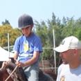הכשרת מדריכי רכיבה טיפולית מדריך וילד רוכב על סוס
