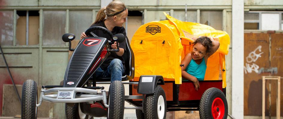 ילדה נוהגת במכונית פדלים עם עגלה נגררת
