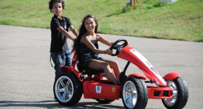 ילדים רוכבים על מכונית פדלים מודל פרארי עם נגרר