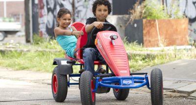ילד מרכיב ילדה על מכונית פדלים עם כיסא נוסף מאחור