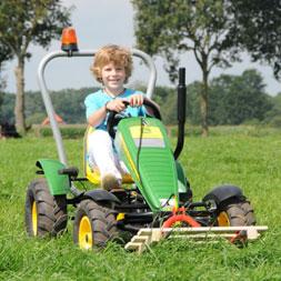 ילד רוכב על טרקטורון פדלים מדגם ג'ון דיר