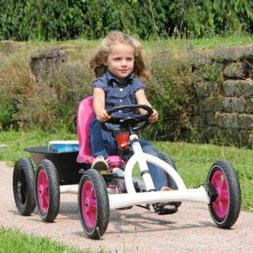 ילדה רוכבת על מכונית פדלים באדי לבנה