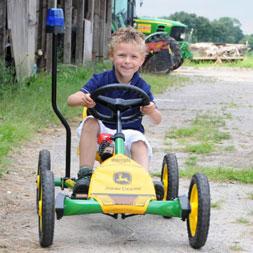 ילד רוכב על מכונית פדלים ג'ון דיר