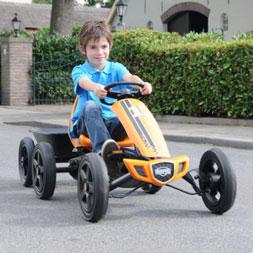 ילד רוכב על מכונית פדלים ראלי כתומה