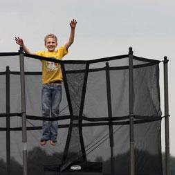ילד קופץ על טרמפולינה עם רשת הגנה