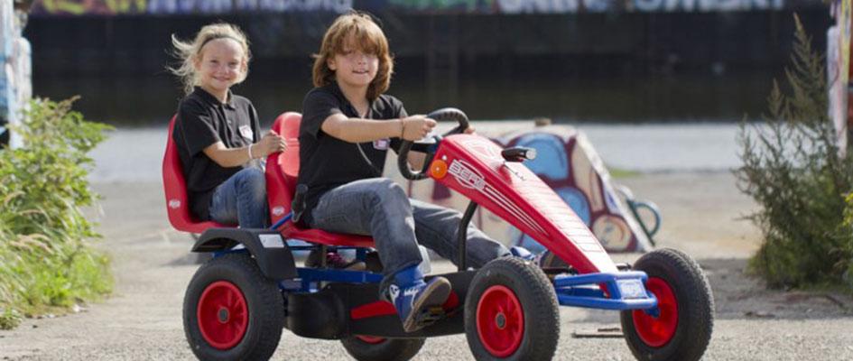 ילדים רוכבים על מכונית פדלים עם כיסא נוסף