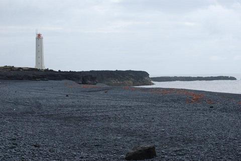 מגדלור על חוף חלוקי בזלת שחורים