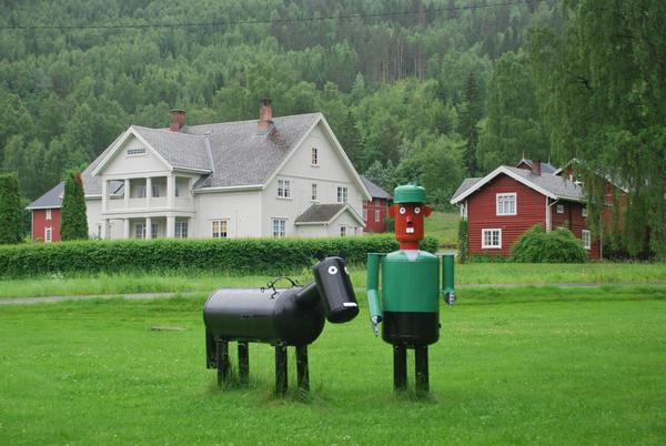 פסל של האיכר והפרה המוצבים על המדשאה שצמודה לכביש