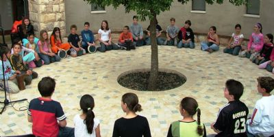 ילדים יושבים במעגל מתופפים עם יוסף המתופף