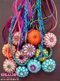60NC- שרשראות תליון פרח ובמרכזו קריסטל. מושלחל על חוטים מסוגים שונים. מגיע במגוון צבעים.