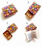 T1- ספר תהילים בתוך קופסת גפרורים- זוהי קופסת גפרורים מצופה עם יריעה של חימר פולימרי שחור ועליו 14 פרחים צבעוניים וספירלות. על החלק העליון פזורים פרחים זהובים ובמרכזם אבני קריסטל צבעוניות ומנצנצות. פנים הקופסה צבוע באקריל זהב. מידות הקופסה הן מידות של קופסת גפרורים רגילה. (SOLD)