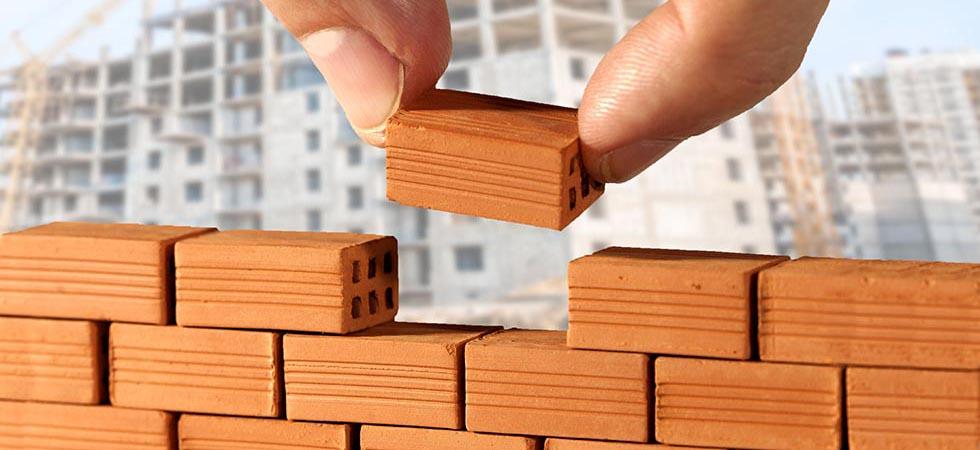 אילוסטרציה של לבני בנייה עם אצבעות שאוחזות